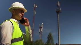 Teléfono masculino de Is Talking On del ingeniero con el director almacen de metraje de vídeo