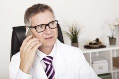 Teléfono masculino del doctor Calling Someone Using fotos de archivo libres de regalías
