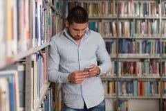 Teléfono masculino hermoso de Typing On Mobile del estudiante universitario Fotos de archivo libres de regalías