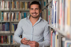 Teléfono masculino hermoso de Typing On Mobile del estudiante universitario Foto de archivo libre de regalías