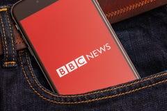 Teléfono negro con el logotipo rojo del BBC News de los medios de noticias en la pantalla foto de archivo libre de regalías