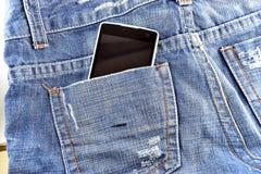 Teléfono negro en sus tejanos del bolsillo Foto de archivo libre de regalías