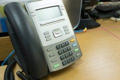 Teléfono negro en trabajo de la tabla Fotos de archivo