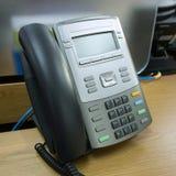 Teléfono negro en trabajo de la tabla Foto de archivo libre de regalías
