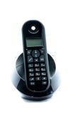 Teléfono negro inalámbrico con la cuna aislada en el fondo blanco Fotos de archivo libres de regalías