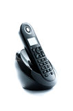 Teléfono negro inalámbrico con la cuna aislada en el fondo blanco Foto de archivo