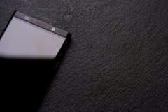 Teléfono negro, piedra negra, cosas duras Imágenes de archivo libres de regalías