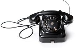 Teléfono negro, viejo o clásico, aislado en un fondo blanco Foto de archivo