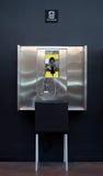 Teléfono público con una silla Fotografía de archivo