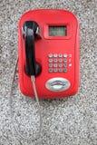 Teléfono público rojo con el microteléfono negro en la pared del granito Fotografía de archivo