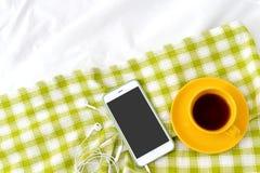 Teléfono plano de la endecha, taza amarilla de té y flores en la manta blanca con la servilleta verde Foto de archivo
