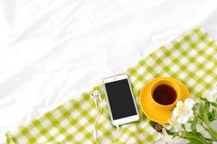 Teléfono plano de la endecha, taza amarilla de té y flores en la manta blanca con la servilleta verde Imagenes de archivo