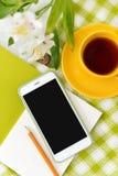 Teléfono plano de la endecha, taza amarilla de té y flores en la manta blanca con la servilleta verde Fotografía de archivo libre de regalías
