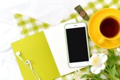 Teléfono plano de la endecha, taza amarilla de té y flores en la manta blanca con la servilleta verde Imagen de archivo
