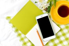 Teléfono plano de la endecha, taza amarilla de té y flores en la manta blanca con la servilleta verde Fotos de archivo