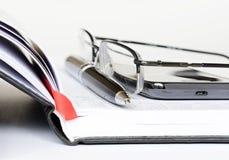 Teléfono, pluma y vidrios en un cuaderno Imágenes de archivo libres de regalías