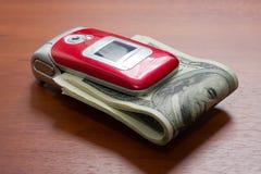 Teléfono portátil con un paquete de dólares Fotos de archivo