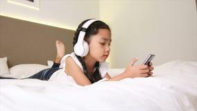 Teléfono principal blanco que escucha de la niña asiática y smartphone móvil con felicidad en la cama almacen de video