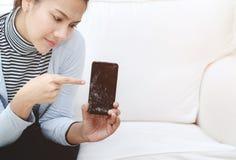 Teléfono que está quebrado en las manos de mujeres imagenes de archivo