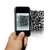 Teléfono que explora un código de QR Imagen de archivo