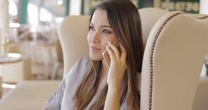Teléfono que habla de la chica joven en butaca almacen de video