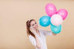 Teléfono que habla de la muchacha mientras que juega con los globos Fotografía de archivo libre de regalías