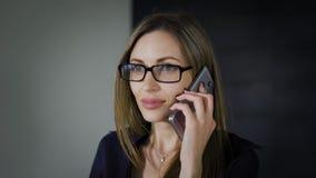 Teléfono que habla de la mujer confiada en oficina El smartphonestanding que habla del empresario de sexo femenino joven confiado metrajes