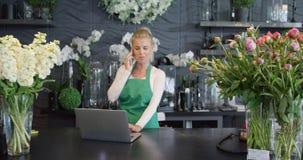 Teléfono que habla de la mujer en tienda floral almacen de video