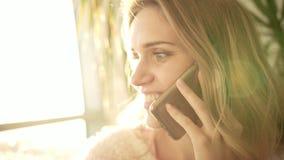 Teléfono que habla de la mujer hermosa Retrato de la sonrisa de la mujer que habla en luz del sol almacen de metraje de vídeo