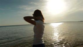 Teléfono que habla de la mujer joven en puesta del sol o salida del sol almacen de metraje de vídeo