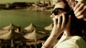 Teléfono que habla de la mujer joven en puesta del sol o salida del sol almacen de video