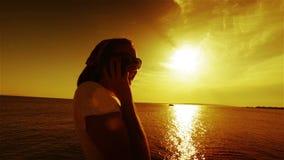 Teléfono que habla de la mujer joven en puesta del sol o salida del sol metrajes