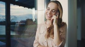 Teléfono que habla de la mujer de negocios en casa de lujo Teléfono móvil de discurso de la mujer relajada almacen de video