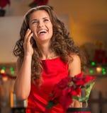 Teléfono que habla del ama de casa joven feliz en cocina de la Navidad Fotografía de archivo libre de regalías