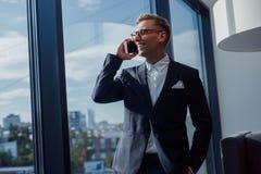 Teléfono que habla del hombre de negocios elegante en oficina Fotos de archivo