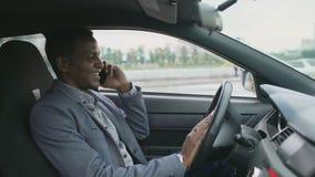 Teléfono que habla del hombre de negocios feliz de la raza mixta mientras que se sienta dentro de su coche al aire libre