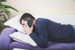 Teléfono que habla del hombre el dormir imágenes de archivo libres de regalías