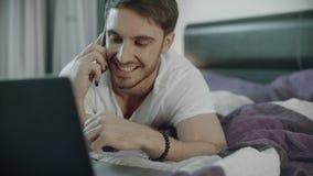 Teléfono que habla del hombre feliz en el sofá en casa Forma de vida de la telecomunicación metrajes