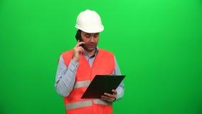 Teléfono que habla del trabajador de construcción con las notas metrajes