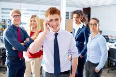 Teléfono que habla ejecutivo joven en equipo étnico multi Fotos de archivo