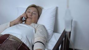Teléfono que habla envejecido del paciente femenino en el lecho de enfermo, dolor de cabeza fuerte repentinamente de sensación almacen de video