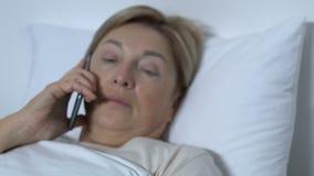 Teléfono que habla paciente femenino en el hospital, sufriendo de dolor, enfermedad incurable almacen de metraje de vídeo
