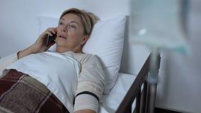 Teléfono que habla y el caer del paciente débil de la señora dormidos en lecho de enfermo cerca de contador del descenso almacen de video