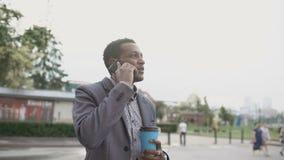 Teléfono que habla y situación del hombre de negocios feliz de la raza mixta con la taza de café al aire libre
