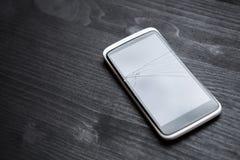 Teléfono quebrado en la tabla en oficina Imágenes de archivo libres de regalías