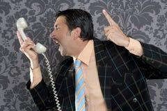 Teléfono retro del hombre de negocios enojado del empollón Imágenes de archivo libres de regalías
