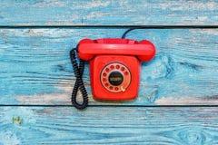 Teléfono retro rojo en el fondo de viejos tableros Foto de archivo