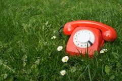 Teléfono rojo al aire libre en la hierba Foto de archivo