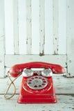 Teléfono rojo en silla de madera fotos de archivo