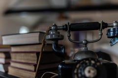 Teléfono rotatorio de la escuela vieja con los libros viejos Imagen de archivo libre de regalías